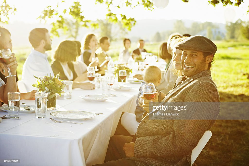 Man sitting at table outside in field laughing : Stock Photo