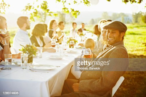 Man sitting at table outside in field laughing : Foto de stock