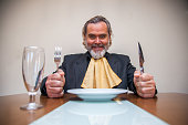 Man ready to eat a meal, holds a knife, a fork and a napkin