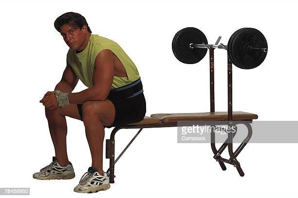 Man sitting at weight bench