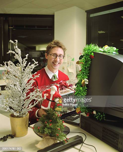 Man sitting at work desk, holding wrapped present