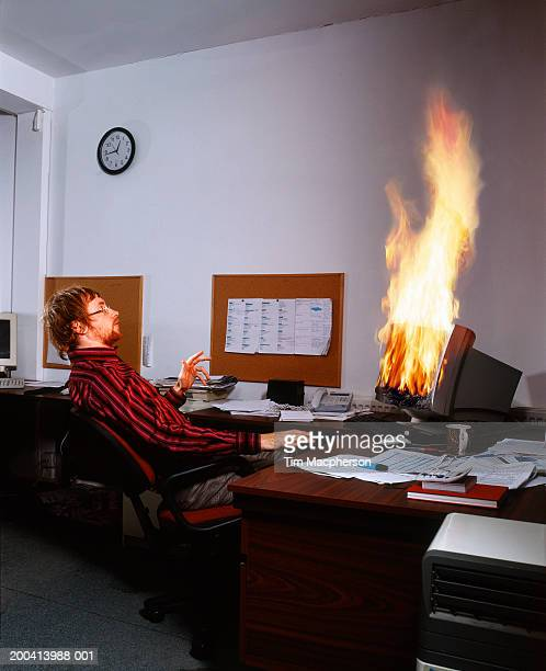 Man sitting back from computer on fire in office (Digital Composite)