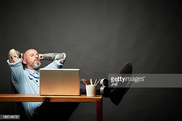 Man sitting back with legs on table