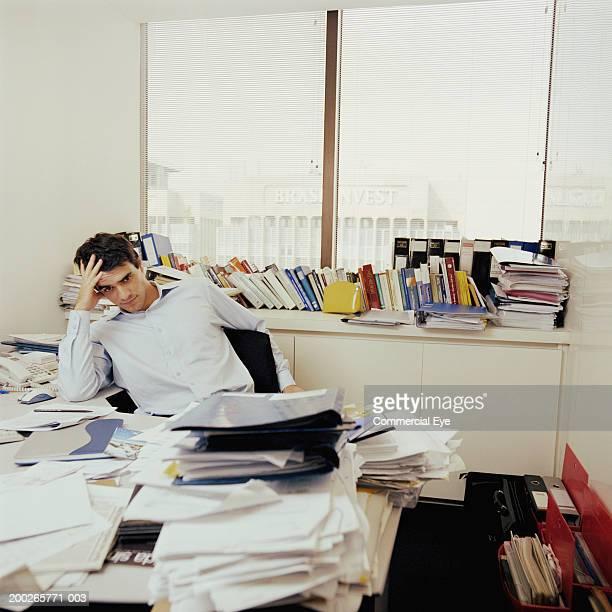 Man sitting behind messy desk (focus on man)