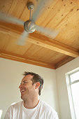 Man sitting beneath ceiling fan, laughing, low angle view