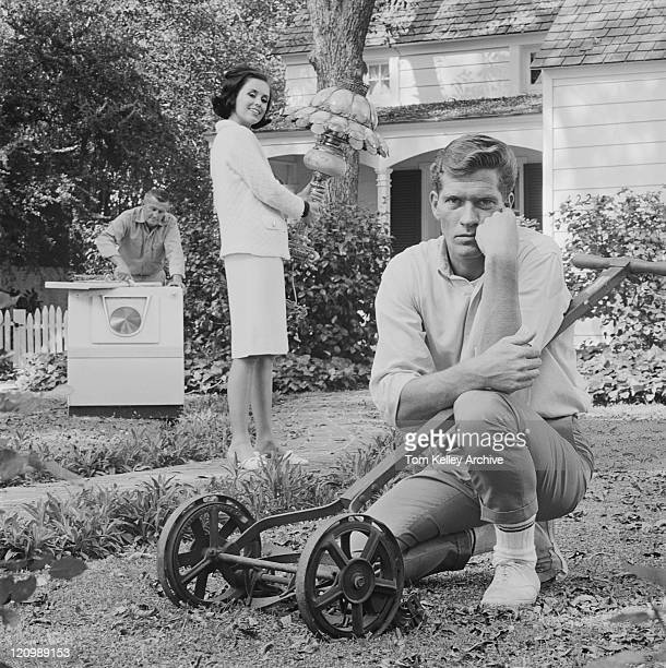 Man sitting beside mower and woman holding lamp in garden