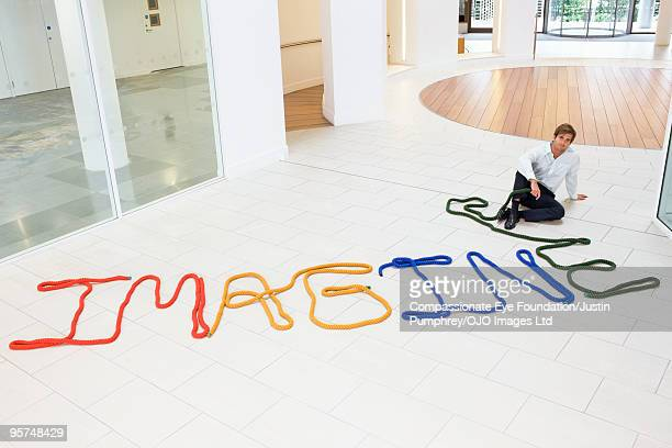 Man sitting beside the word imagine