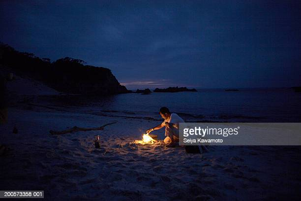 Man sitting by campfire on beach at night