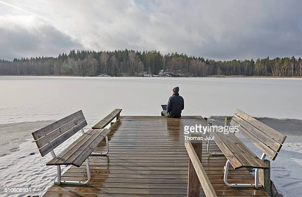 Man Sitting By frozen Lake With Laptop