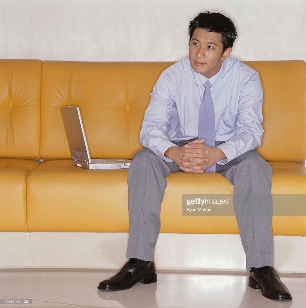 Man Sitting By Laptop On Yellow Leather Couch Indoors : Stock Photo