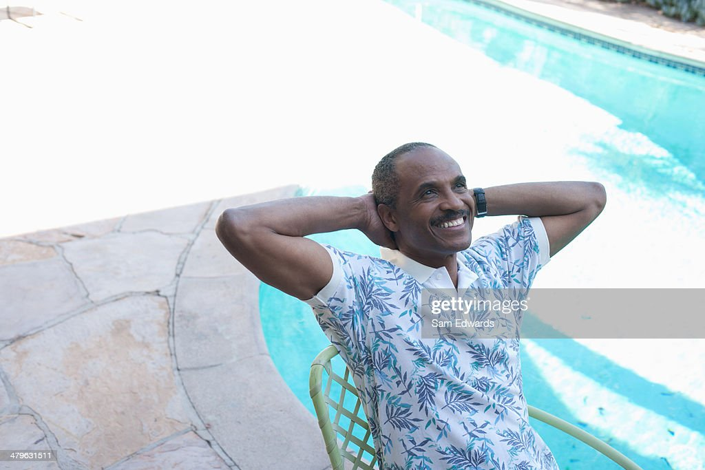 Man sitting by pool : Stock Photo