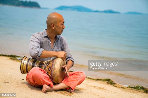 Man sitting by the sea playing a percussion instrument