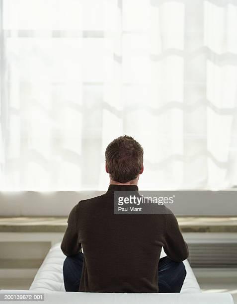Man sitting cross-legged, rear view