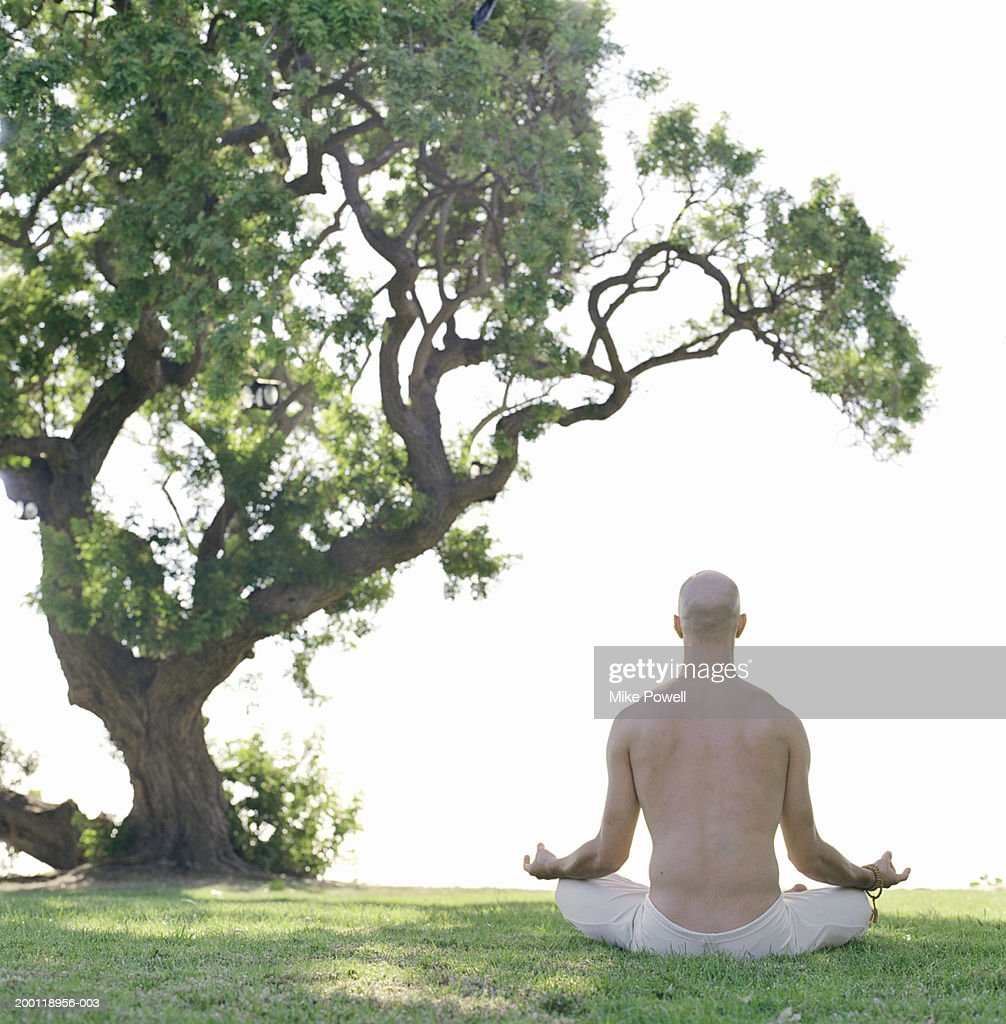 Man sitting doing yoga meditation pose, rear view, outdoors : Stock Photo