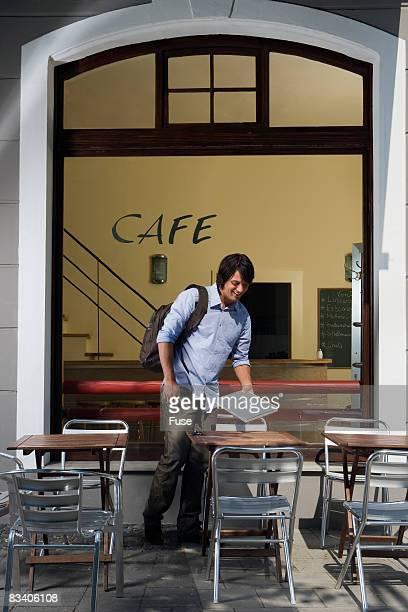 Man Sitting Down at Sidewalk Cafe