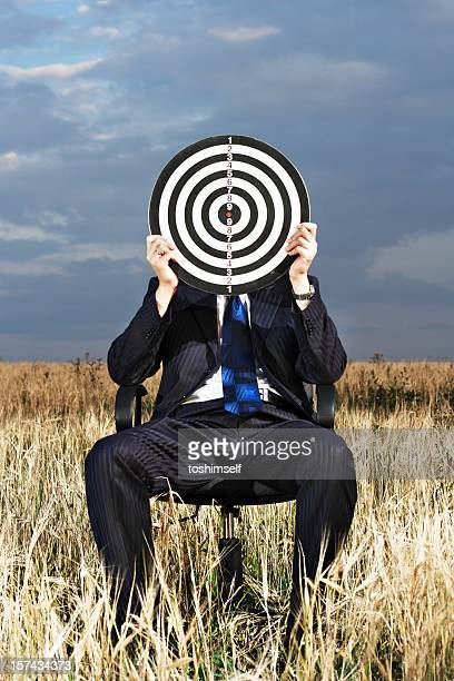 A man sitting down holding a target board up to his face