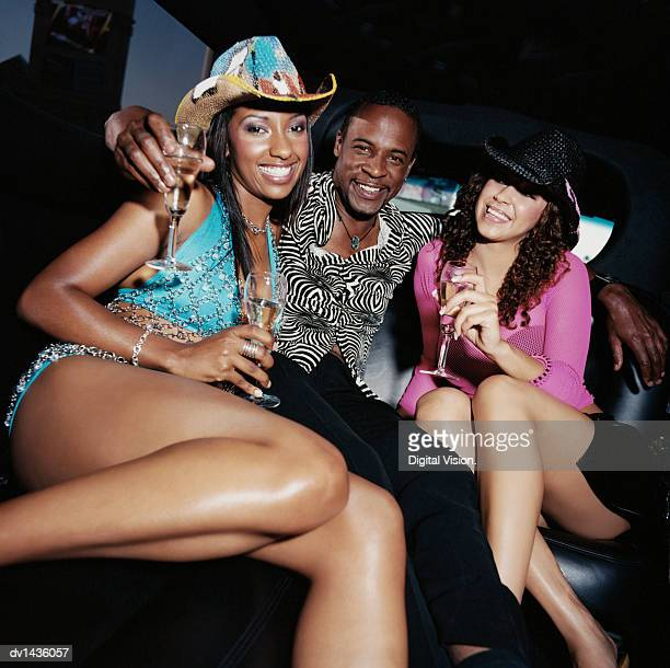 Man Sitting in a Back Seat of a Limousine With His Arms Around Two Women, Holding Wineglasses