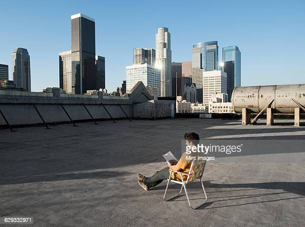 A man sitting in a beach chair on a city rooftop reading.