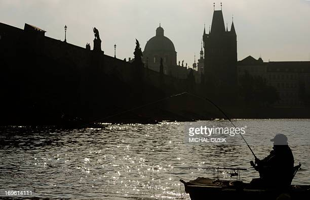 A man sitting in a boat fishes on the river Vltava near the Charles Bridge on May 29 2013 in Prague AFP PHOTO / MICHAL CIZEK