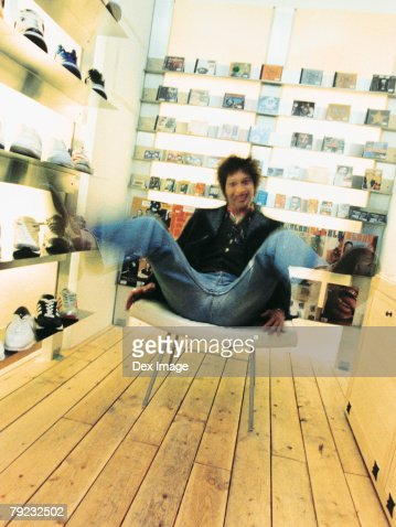 Man sitting in a cushion chair, legs raised, book shelve in background : Stock Photo