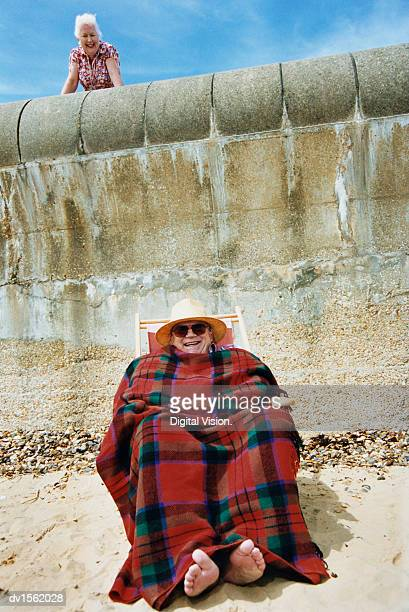 Man Sitting in a Deck Chair on a Beach Wrapped in a Blanket and His Wife Watching