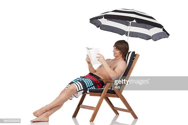 Man sitting in a deck chair reading book
