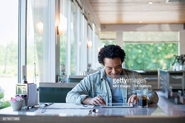 A man sitting in a diner using a digital tablet.