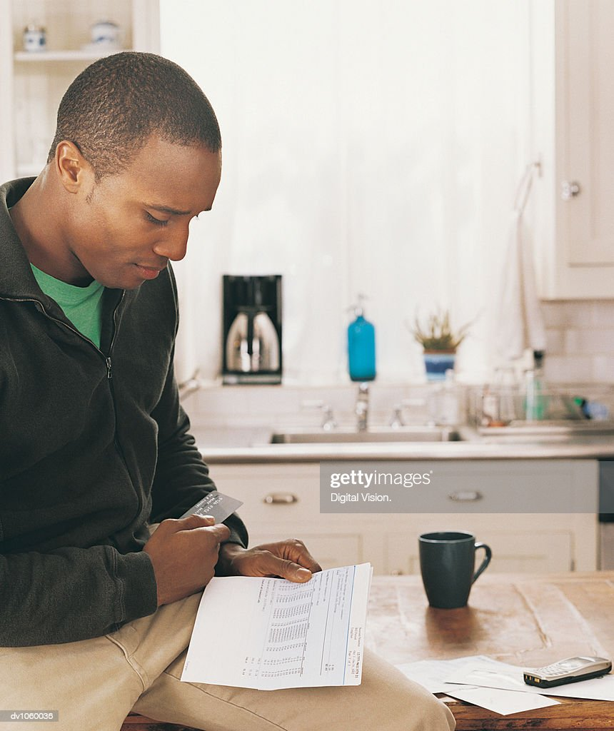 Man Sitting in a Kitchen Looking at a Bank Statement