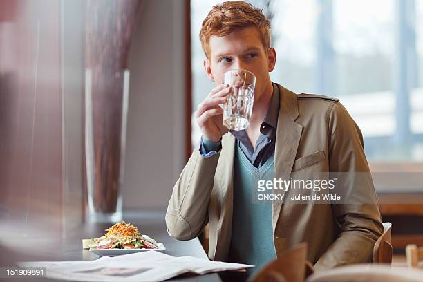 Man sitting in a restaurant and drinking water