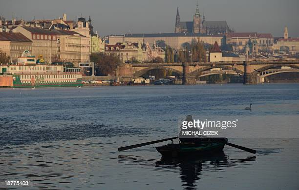 A man sitting in a rowing boat fishes on Vltava river during a sunny autumn day on November 12 2013 in Prague Prague castle is seen in background AFP...