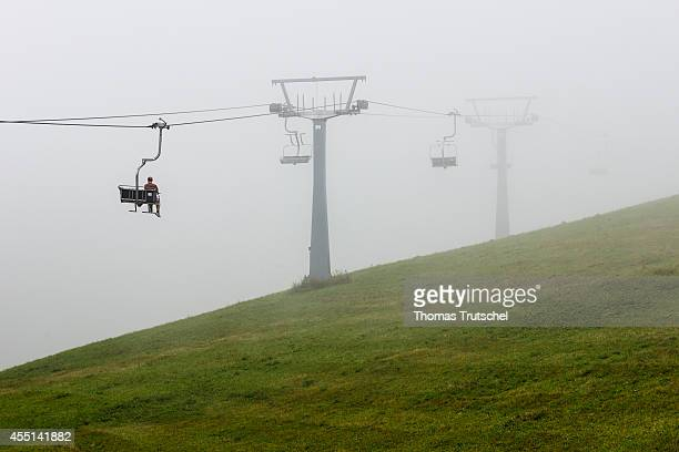 Man sitting in an almost empty chairlift disappearing in the mist on August 21 in Schmitten Austria
