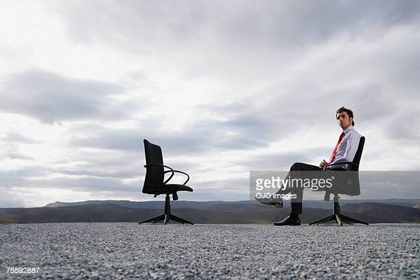 Man sitting in an office chair outdoors