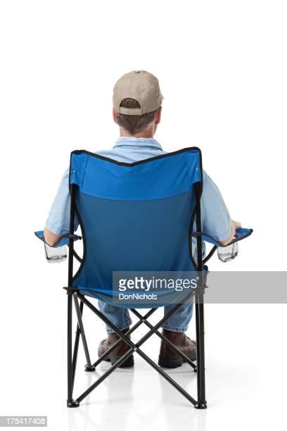 Mann sitzt im Freien Klappstuhl