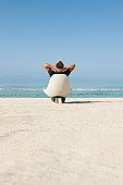 Man sitting in armchair on beach looking at ocean, rear view