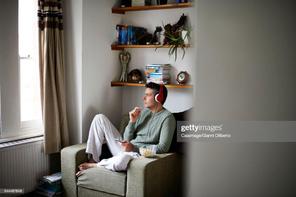 Man sitting in armchair with headphones looking through window