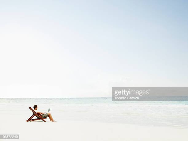 Man sitting in beach chair working on laptop