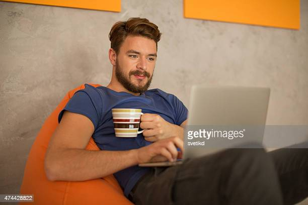 Man sitting in bean bag and using laptop.