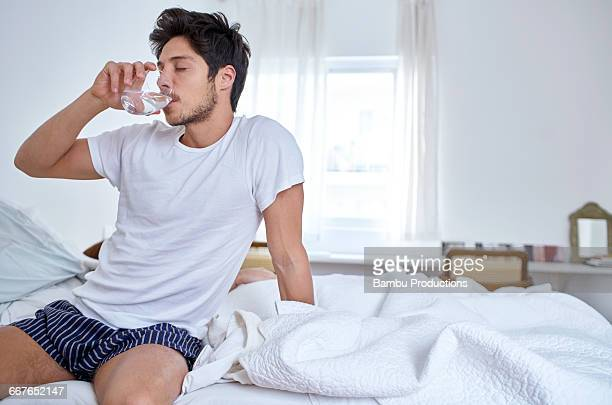 Man sitting in bed drinking water