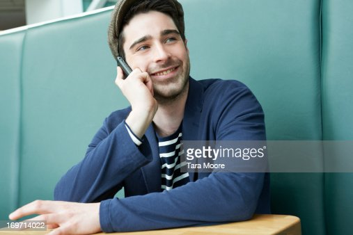man sitting in cafe talking on mobile : Stock Photo