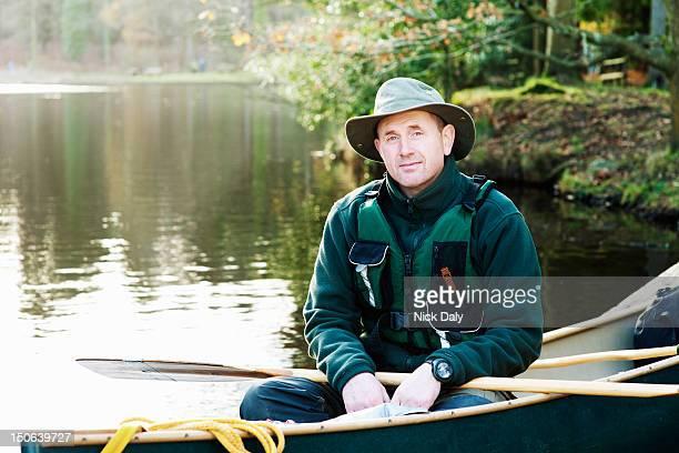 Man sitting in canoe on still lake