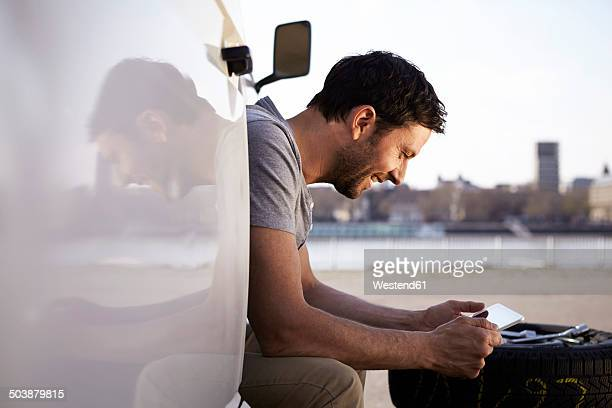 Man sitting in car looking at digital tablet