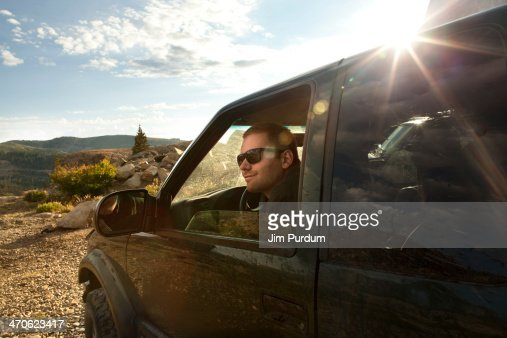 Man sitting in car overlooking rural landscape