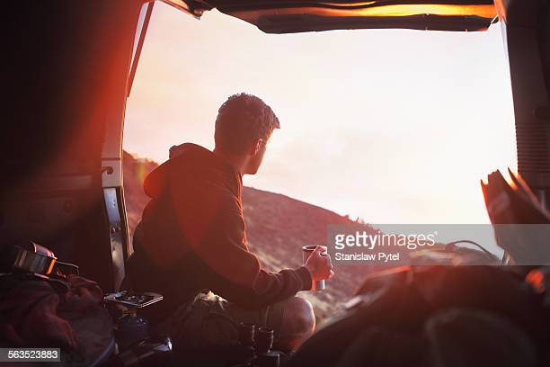 Man sitting in car trunk, looking at sunset