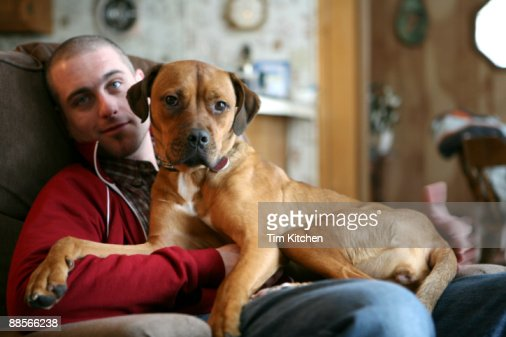 Man sitting in chair, dog on lap : Stock Photo