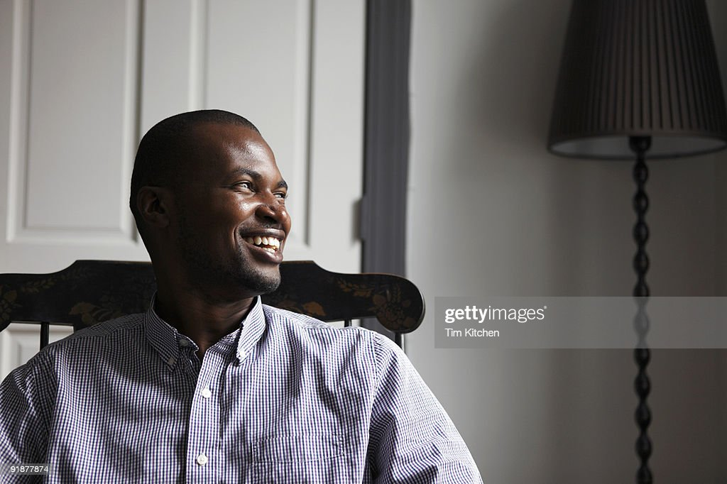 Man sitting in chair, laughing, profile : Stock Photo