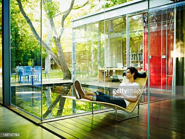 Man sitting in chair looking across courtyard