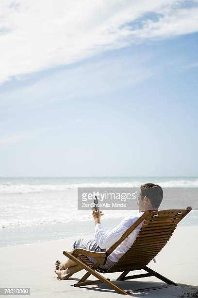 Man sitting in chair on beach, using cell phone, side view
