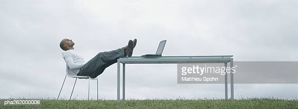 Man sitting in chair outdoors with feet on table and laptop on table, in front of overcast sky