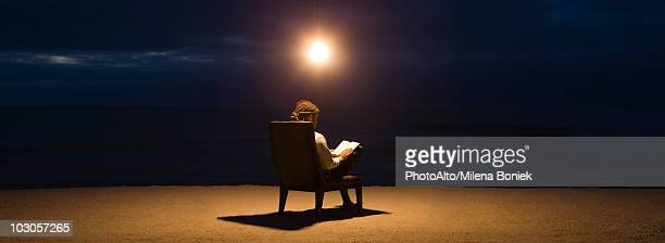 Man sitting in chair under light bulb on beach at night, reading book
