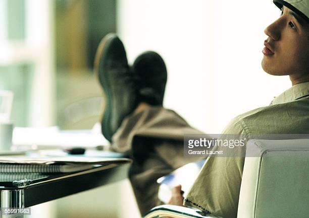 Man sitting in chair with feet on table, looking to the side, rear view.